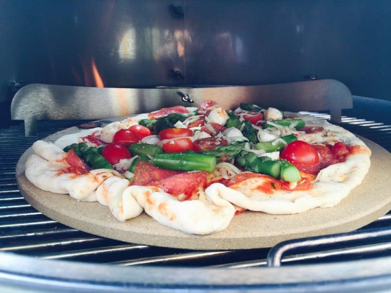 Frischer Pizzateig mit leckeren Zutaten direkt aus dem Grill