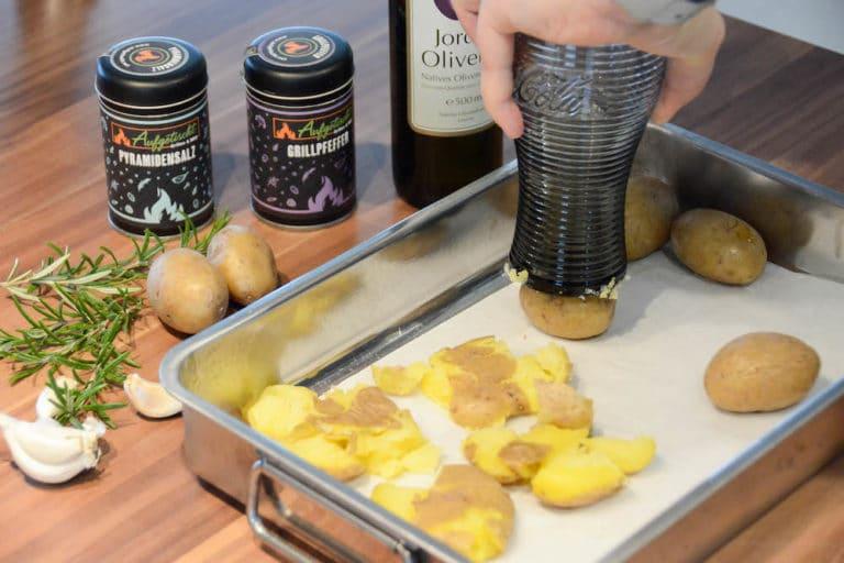 Die Kartoffeln mit einem Glas zu Stampfkartoffeln machen